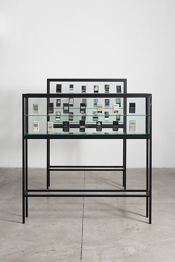 Assaf Shaham, Figures (Hell), 2014, metal, black paint, plexiglas, glass, calculators (18 units),125 x 25 x 175 cm. Figures (Hole), 2014, metal, black paint, plexiglas, glass,, calculators (14 units)